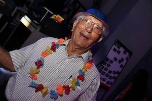 תמונה של סבא רוקד במהלך אירוע ויש לו שרשרת הוואי צבעונית וכובע צבעוני כל הכבוד לסבא שקם לרקוד